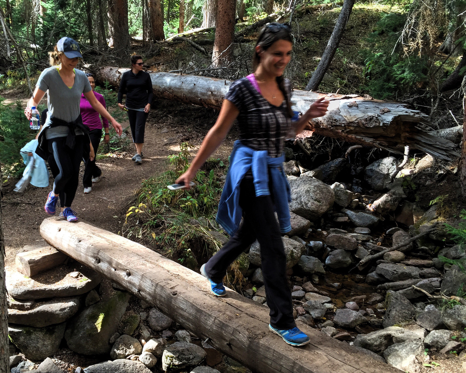The group navigates a log bridge along the Piney Lake Trail