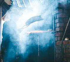 A three-chambered brick smoker dominates the patio of Woodyard Bar-B-Que.