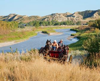 Interpreters drive a stagecoach near Chateau de Mores State Historic Site.