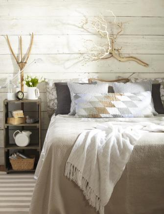Quilts and ticked pillows on silk, modern, contemporary bed.