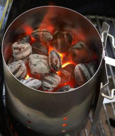 A metal chimney helps start a charcoal grill.